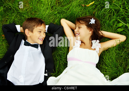 Portrait of smiling children bride and groom lying on green grass and looking at on another - Stock Photo