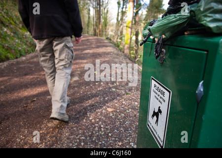 Overflowing Dog waste bin on footpath walker on path - Stock Photo