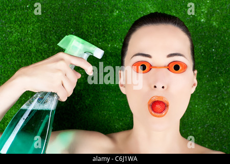 Closeup of a beautiful woman wearing tanning bed glasses with strawberry in mouth and spray bottle in hand against - Stock Photo