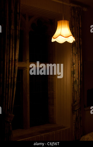 Ghostly lamp in a dimly lit room - Stock Photo