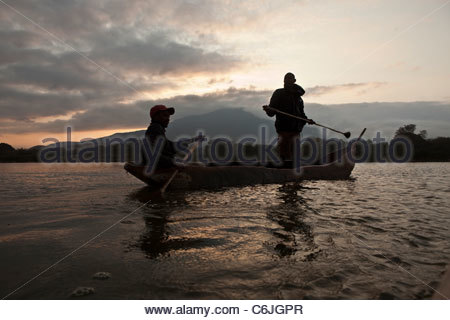 Two fishermen in a dugout canoe on Lake Babati at sunrise - Stock Photo