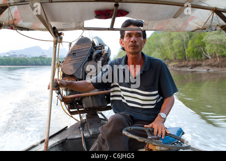 asian man driving long tailed boat in Krabi river, thailand - Stock Photo