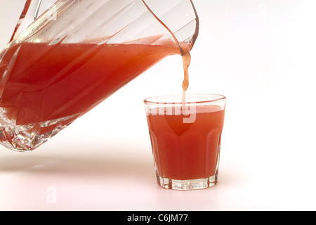 Pouring a glass of freshly squeezed pink grapefruit juice on a white background - Stock Photo