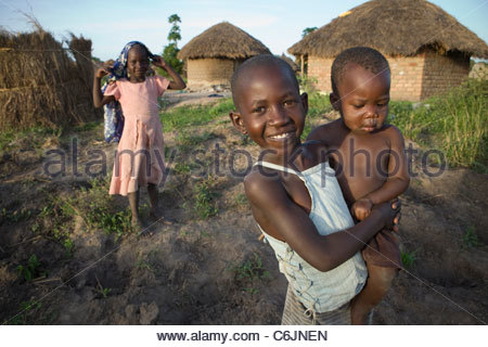 Two young girls, one holding her baby brother on her hip - Stock Photo
