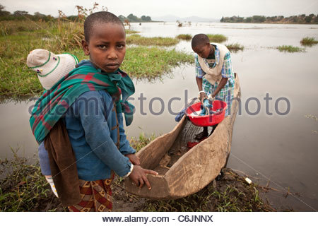 Two young girls on the shore of Lake Babati, one with a baby on her back and the other standing in a dugout canoe - Stock Photo