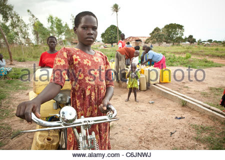 Young girl carrying filled water canisters on her bicycle - Stock Photo