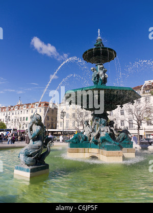 Baroque fountain on rossio square the liveliest placa in Lisbon with wavy cobble stone pattern, Portugal - Stock Photo