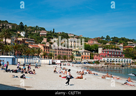 Swimmers and sunbathers take advantage of the sunshine on the beach in front of the elegant buildings of Santa Margherita - Stock Photo