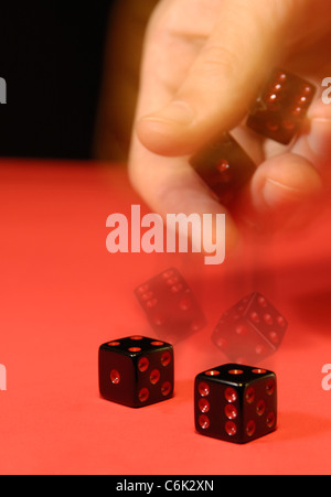 Hand rolling the dice Artistic multiple exposure image showing motion in action - Stock Photo
