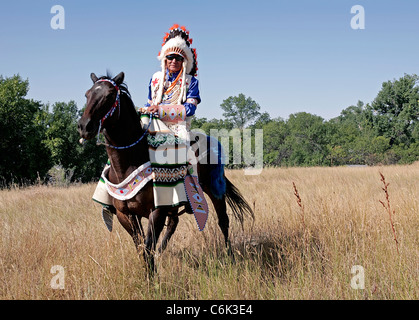 Crow chief in warbonnet and full regalia on the Crow Reservation, Montana. - Stock Photo