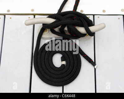 Neatly coiled mooring rope tied around cleat - Stock Photo