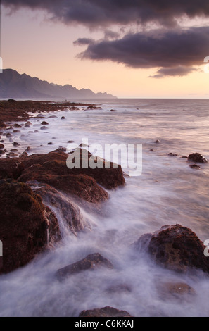 Sunset from Agaete on the north coast of Gran Canaria, Canary Islands, Spain. A man fishing from rocks in distance - Stock Photo