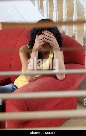 young dark haired woman sitting alone on a red sofa, covering her face. - Stock Photo