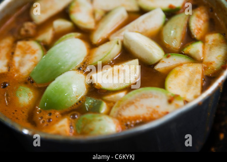 Cooking eggplant in pork stock and curry paste mixture - Stock Photo