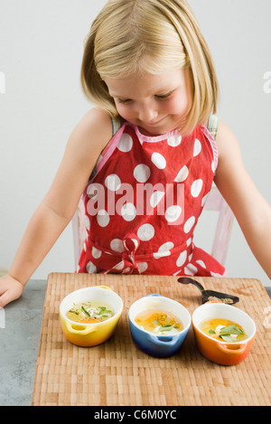 Little girl preparing baked eggs in small casserole dishes - Stock Photo