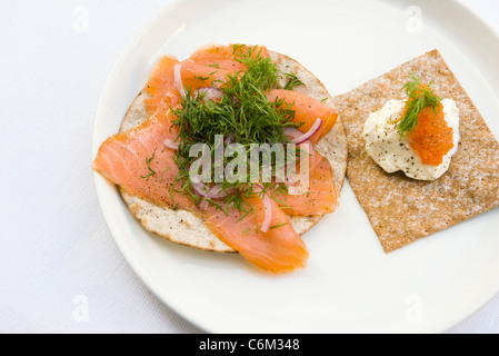 Crisp bread topped with smoked salmon and fresh dill, sour cream and salmon roe - Stock Photo