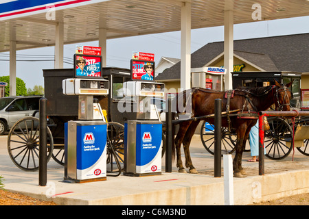 Amish horse and buggy hitched near a service station gasoline filling station in Shipshewana, Indiana, USA. - Stock Photo