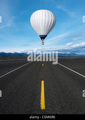hot air balloon floating over blacktop highway running through landscape of black sand - Stock Photo