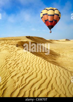 hot air balloon floating over sand dunes at Oceano Dunes, Pismo Beach, California - Stock Photo