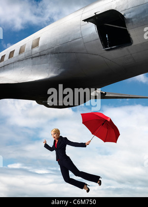 humorous image of woman holding umbrella falling from open hatch of airplane in flight - Stock Photo