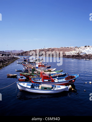 Small fishing boats in the harbour with apartment blocks to the right, Puerto del Carmen, Lanzarote, Canary Islands, - Stock Photo