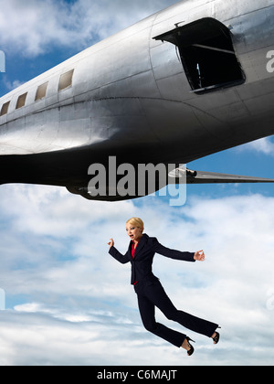 humorous image of woman falling from open hatch of airplane in flight - Stock Photo