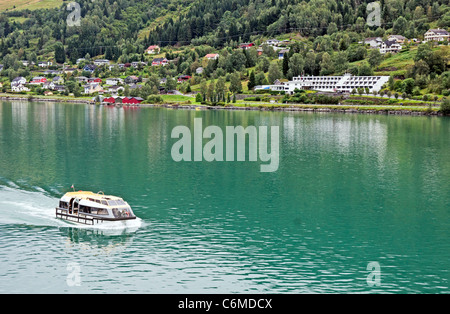 A tender is carrying passengers from a cruise liner to Olden pier on the Innvikfjorden in Norway with Olden Fjordhotel - Stock Photo