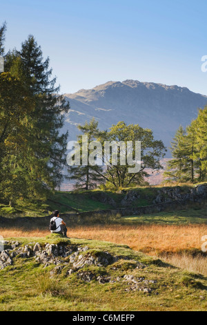 An Asian woman sits and enjoys the view on a hike in the Lake District, UK - Stock Photo