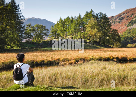 A young Indian Asian woman rests on a hike in the English countryside