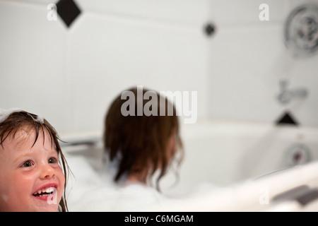 Girls playing in bubble bath. - Stock Photo