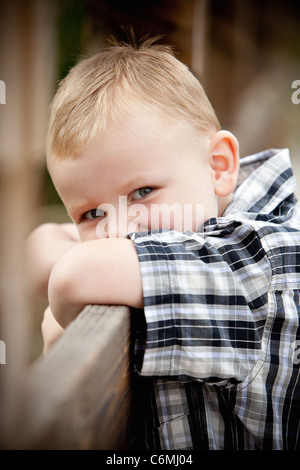 Young boy sneaking a glance leaning on a fence - Stock Photo