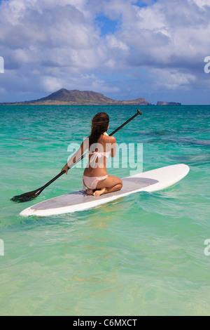 beautiful polynesian girl on a standup paddle board - Stock Photo