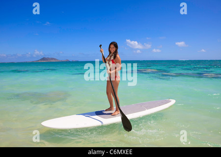 beautiful polynesian girl on a stand up paddle board - Stock Photo