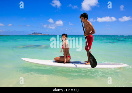 young couple with their paddle board in hawaii - Stock Photo