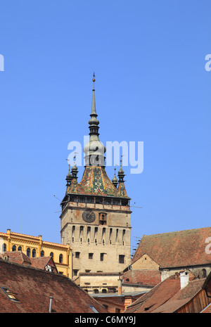 Image of the Clock Tower over the houses roofs in Sighisoara,Romania. - Stock Photo