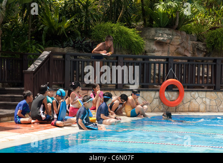 Primary schoolchildren having a swimming lesson with their teacher, Singapore, Asia - Stock Photo