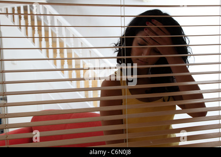Woman behind a wooden blind hand on her head. - Stock Photo