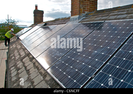 Photovoltaic panels on a roof using solar energy to create electricity - Stock Photo