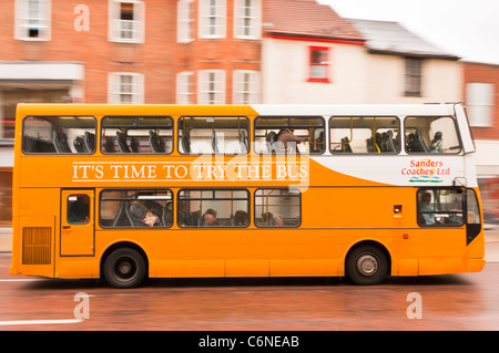 A double decker bus drives through the city showing deliberate motion blur in Norwich , Norfolk , England , Britain - Stock Photo