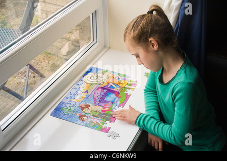 Eleven year old girl doing a jigsaw puzzle. - Stock Photo