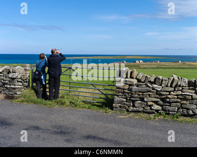 dh  PAPA WESTRAY ORKNEY Two birdwatchers viewing grass fields with binoculars people birds watchers - Stock Photo