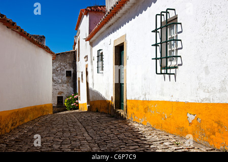 Narrow cobbled street in old medieval Obidos village, Portugal. Houses with white walls and yellow strips. - Stock Photo