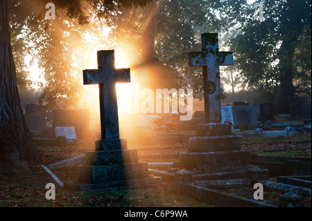 Cemetery Cross headstones lit up in the early morning sunlight through mist. England - Stock Photo
