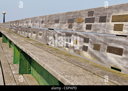 Brass plaques along the bench seating on Clevedon Victorian Pier - Stock Photo