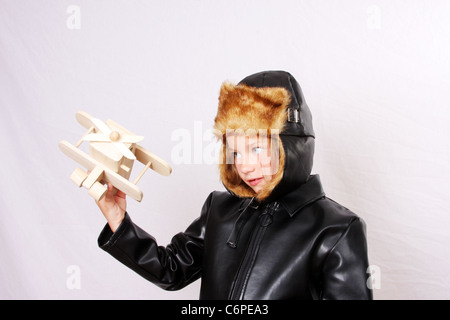A young girl pretending to be a pilot while playing with a wood toy plane. Focus on the plane - Stock Photo