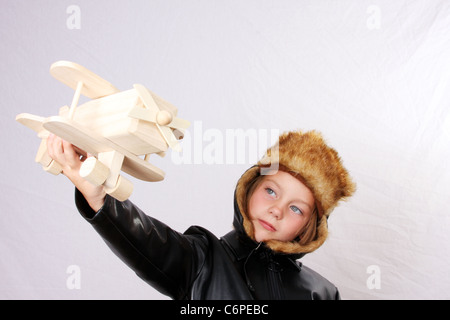 A young girl pretending to be a pilot while playing with a wood toy plane. Plane in focus - Stock Photo