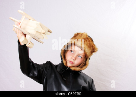 A young girl pretending to be a pilot while playing with a wood toy plane. Plane in focus. - Stock Photo