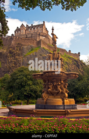 Edinburgh Castle on volcanic castle rock from West Princes Street Gardens with Ross Fountain sculpture by Jean-Baptiste - Stock Photo