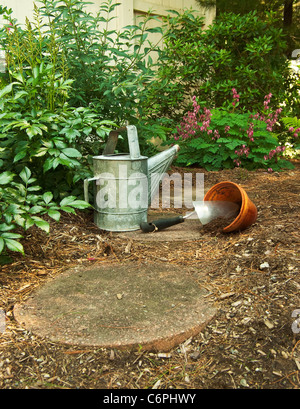 An old watering can sits next to a trowel and clay pot that are ready for flowers - Stock Photo