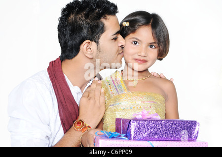 On Rakshabandhan, beautiful little girl is happy after receiving gifts and brother is kissing her with love. - Stock Photo